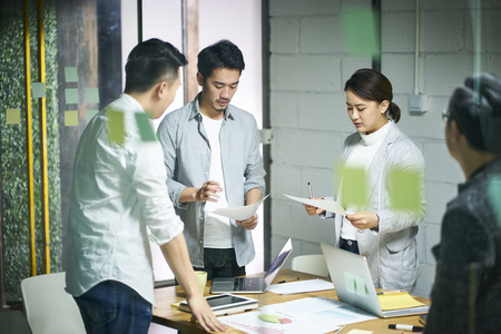 young asian entrepreneurs of small company discussing business plan in office meeting room.