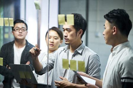 jeune entrepreneur asiatique d'une petite entreprise dessinant un diagramme sur du verre lors d'une réunion d'équipe discutant et analysant la situation de l'entreprise au bureau. Banque d'images
