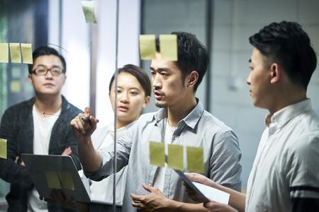 jonge aziatische ondernemer van klein bedrijf dat een diagram op glas trekt tijdens teamvergadering die de bedrijfssituatie op kantoor bespreekt en analyseert. Stockfoto