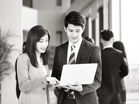 young asian businessman and businesswoman working together in office using laptop computer, colleagues talking in background, black and white.