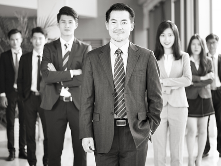 portrait of a team of successful asian businessmen and businesswomen, looking at camera smiling, black and white.