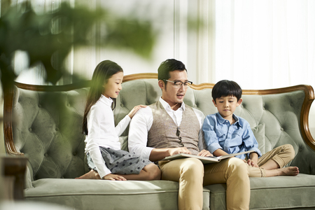 young asian father and two children sitting on couch reading book together in  living room at home