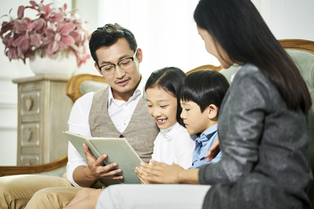 Young asian parents and two children sitting on couch reading book together in  living room at home Imagens