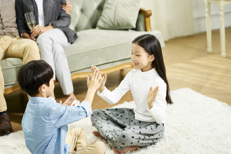 Two cute little asian kids sitting on carpet playing game with parent sitting on sofa in the background 版權商用圖片