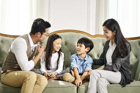 young asian father and mother and two children sitting on couch chatting in family living room at home