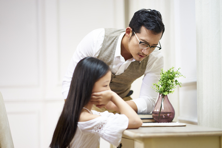 young asian father looking at what's written or drawn by his unhappy daughter.