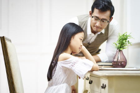 sad little asian girl sitting at desk in her room and getting comfort from caring father