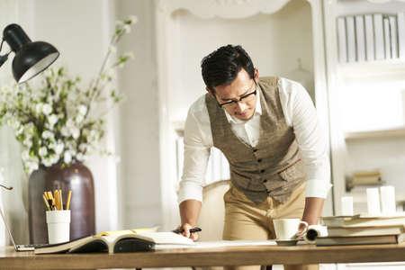 giovane designer architetto asiatico in piedi davanti alla scrivania che lavora a casa