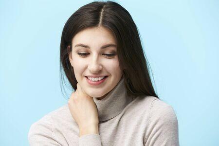 ritratto in studio di una giovane e bella donna caucasica, guardando in basso e sorridente, isolato su sfondo blu