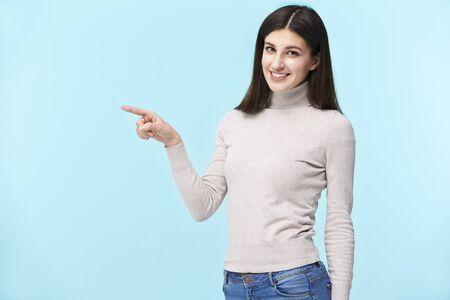 Portret van een mooie jonge blanke vrouw, naar links wijzend met de vinger, kijkend naar de camera glimlachend, geïsoleerd op blauwe achtergrond