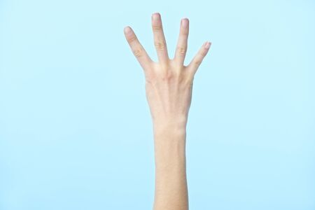human hand showing number four, isolated on blue background