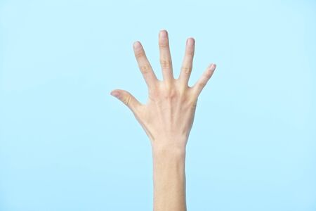 human hand showing number five, isolated on blue background Banco de Imagens