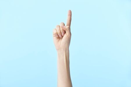 human hand showing number one, isolated on blue background