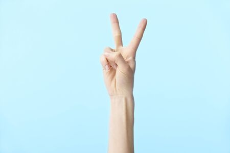 human hand showing number two, isolated on blue background