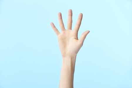human hand showing number five, isolated on blue background Stock Photo