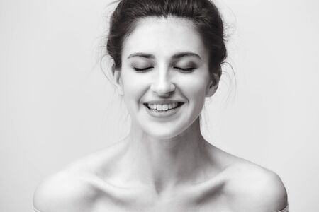 black and white portrait of a beautiful caucasian woman, eyes closed, happy and smiling
