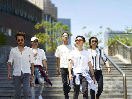 a group of five young asian adults hanging out together walking on street Banco de Imagens