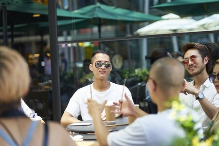 young asian people man and woman relaxing chatting in outdoor coffee shop Banco de Imagens