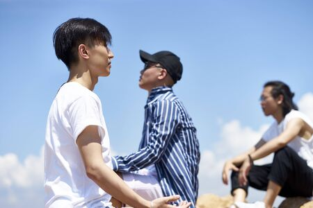 group of young asian adult men sitting on top of rocks against blue sky enjoying sunshine and fresh air Banco de Imagens
