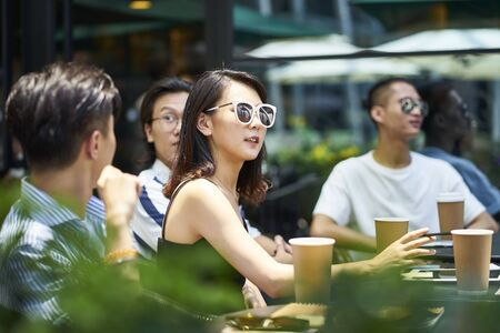 young asian adult friends gathering relaxing in outdoor coffee shop Banco de Imagens