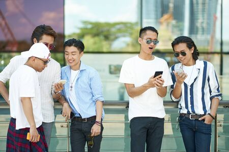 young asian adult men using social media looking at mobile phone together Banco de Imagens