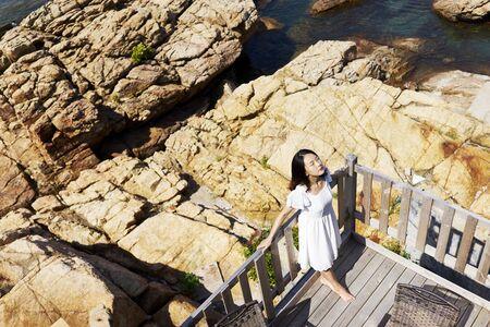 young asian woman enjoying sunshine on balcony by sea