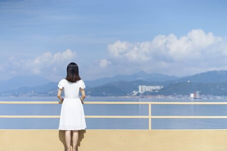 rear view of a young asian woman in white shirt looking at sea Banco de Imagens