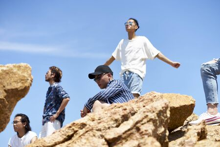 group of young asian adult men standing on top of rocks against blue sky enjoying sunshine and fresh air
