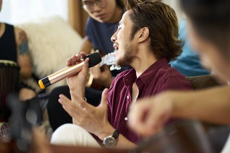 young asian adult men rock band members rehearsing singing playing musical instruments in living room of a house