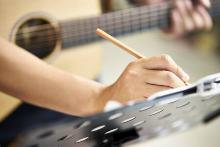 close-up shot of hand of a guitarist taking notes while composing music