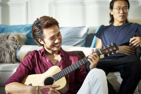 asian young adult men relaxing and enjoying music and beer at party Banco de Imagens