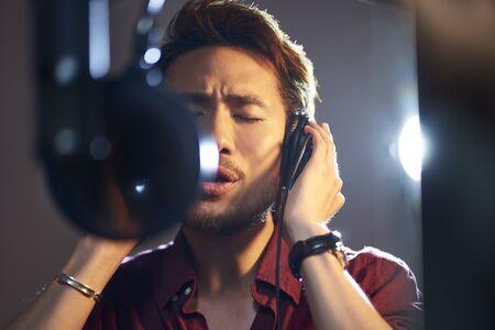 young asian adult man enjoying singing a song in modern recording studio