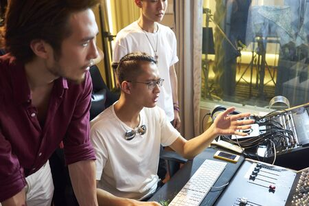 young members of an asian rock band working together editing music using computer