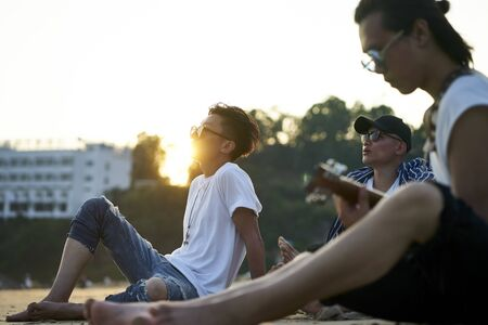 three young asian adult men sitting on sand beach playing guitar at dusk