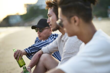 three young asian adult men sitting on beach drinking beer