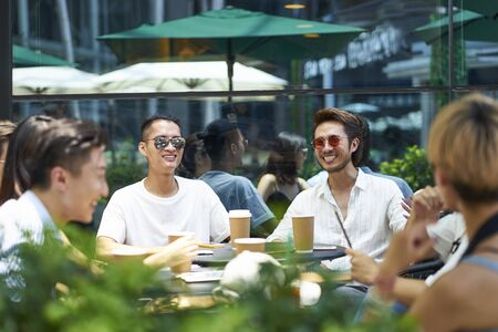 group of happy young asian adults sitting outdoors talking chatting and drinking coffee