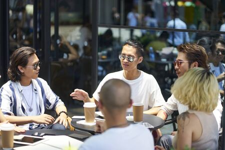 young asian college students having a group discussion at an outdoor coffee shop