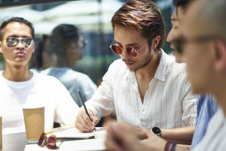 Grupo de jóvenes estudiantes universitarios asiáticos que estudian juntos en una cafetería al aire libre Foto de archivo