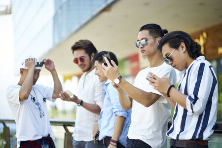 group of five young asian men playing with cellphones outdoors Reklamní fotografie - 129550761