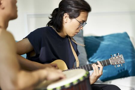 young asian  guitarist sitting on couch playing guitar Reklamní fotografie - 129550813