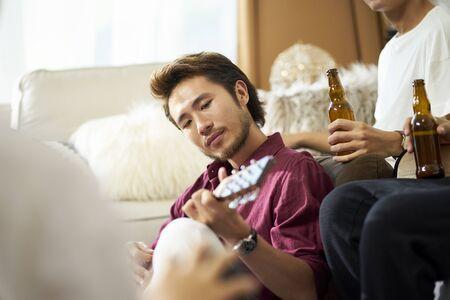 young asian adult men drinking beer at home Reklamní fotografie