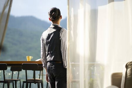 young asian man standing on patio looking at mountain view
