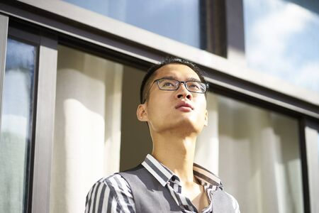 young asian man standing on patio looking at view Reklamní fotografie - 129686465