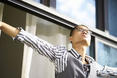 young asian man standing on patio enjoying fresh air with open arms