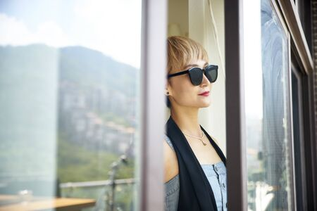 asian woman wearing sunglasses looking at view by the window Reklamní fotografie