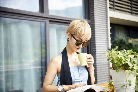 young asian woman enjoying reading and coffee on patio Reklamní fotografie - 129686511