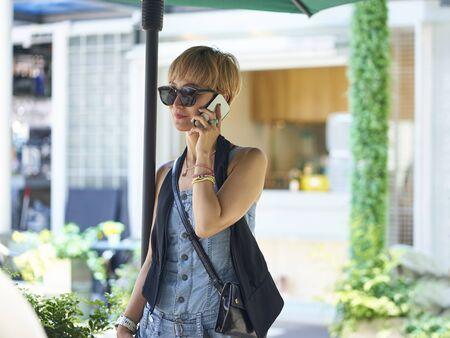 asian woman talking on cellphone while walking Reklamní fotografie - 129686532