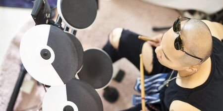 high angle view of a young asian drummer percussionist beating electronic drums Reklamní fotografie