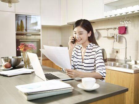 young asian woman sitting at kitchen counter working using laptop talking on cellphone.
