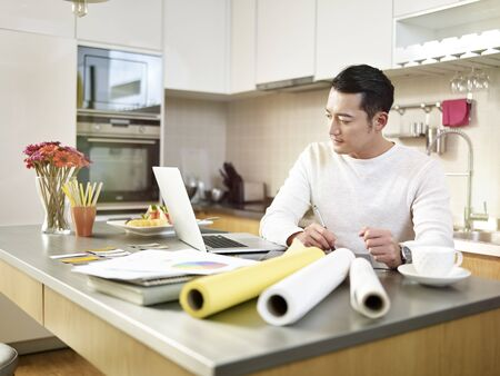 young asian designer sitting at kitchen counter creating a design using pen and laptop.
